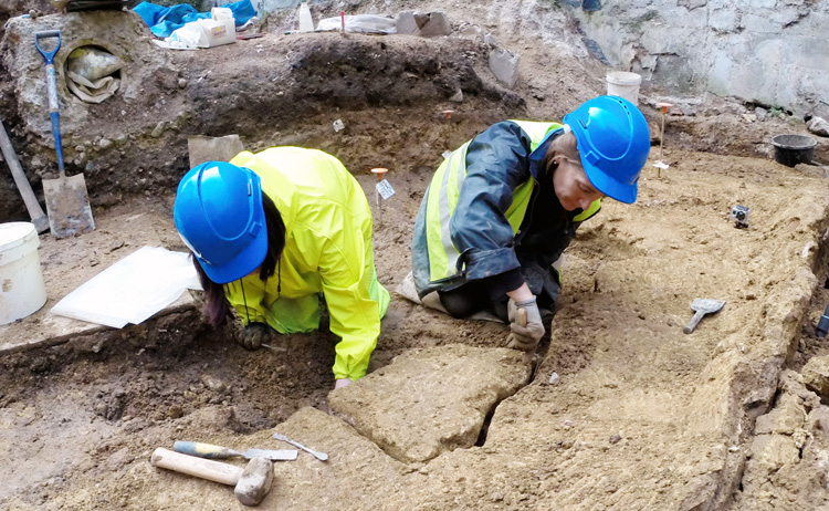Conservators from MOLA removing a section of the 1st century upturned Roman wall plaster © MOLA