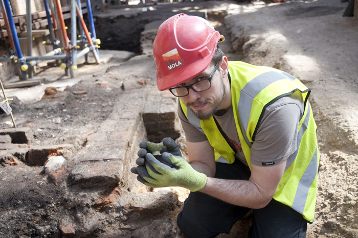 Archaeologist Paul McGarrity holds a 16th century bird whistle, a possible theatrical sound effect, discovered at Curtain theatre (c) MOLA