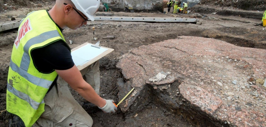 A MOLA archaeologist measures a section of mosaic floor discovered within one of the Roman rooms.
