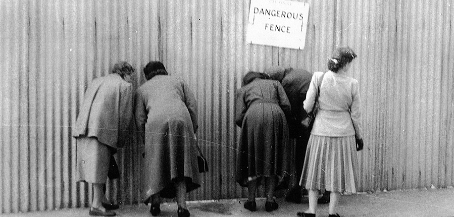 Ladies peer through a hole in the Temple of Mithras site fence (c) John Christopher Pegg