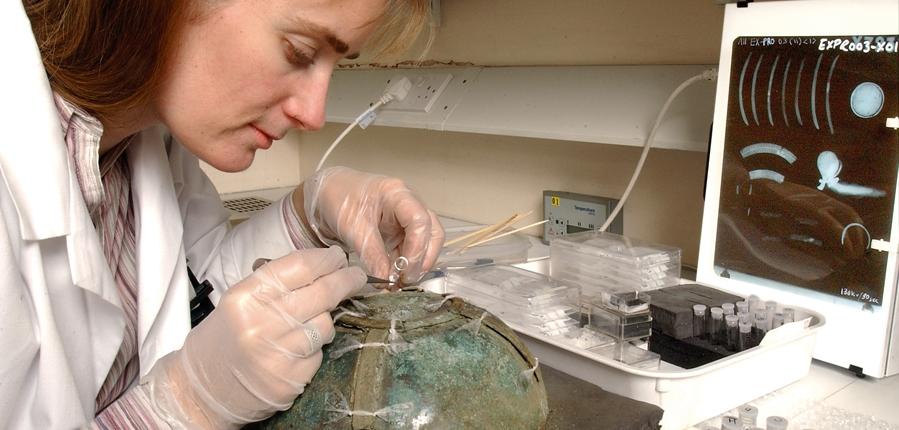 MOLA conservator Liz Barham studieds the hanging bowl (c) MOLA