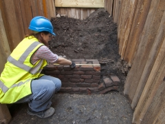 Trail excavation at the Curtain Theatre revealed a brick wall thought to support inside timber frame of the playhouse (c) MOLA
