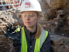 An archaeologist holding the finial of a money pot found on site at the Boar's Head Playhouse (c) MOLA