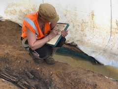 An archaeologist records human remains at Great Ryburgh (c) MOLA