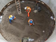 Archaeologists excavating burials.
