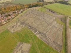 Aerial photograph of the main excavation area, clearly showing the field system defined by ditches and a series of probable round houses. The light lines crossing the site are scars from later ploughing.