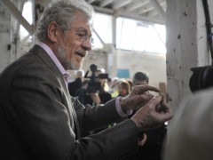 Sir Ian examines a 16th-century pottery fragment found on the site.