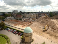 The same position and line of sight as the previous photo, but zoomed back to include the domed roof of the Old Observatory's Heliometer building in the foreground, and the remains of some the 20th century infirmary buildings beyond the trenches.