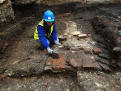 n archaeologist cleaning the brick remains.