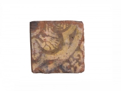 Part of a four-tile panel from a tilery at Penn, Buckinghamshire dating to around 1350–1390. The tile depicts a strange mythical creature with a human head at one end and a leaf-like tail at the other © MOLA