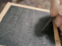 Writing in cursive Latin on a reconstruction waxed writing tablet (c) NextShoot