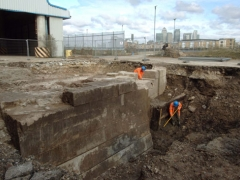 Archaeologists clean the west wall of the Great Dock during the evaluation
