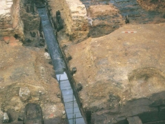 The Roman civic waterfront at Pudding Lane, looking north into the surviving bases of the warehouses adjacent, also with a dugout  timber drain, all preserved by deep burial and waterlogging for just under 2000 years