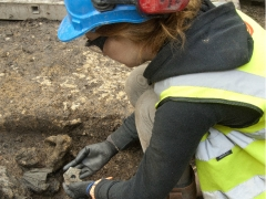 An archaeologist lifting a rare enamelled container