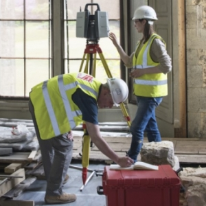 Two buildings archaeologists in yellow hi vis vests and white hard hats record a room