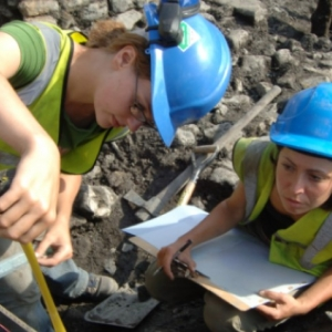 Two archaeologists in blue hard hats and yellow hi vis vests measuring a feature