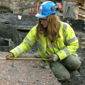 An archaeologist with long hair, wearing a blue hard hat and hi vis vest, measures a mosaic floor