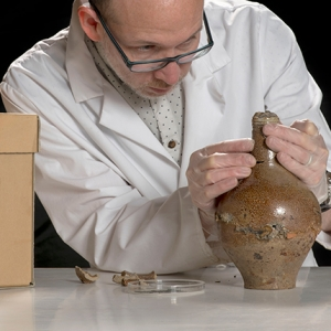 MOLA Finds Specialist Nigel Jeffries inspects a 'witch bottle' found during excavations at Holywell Priory (c) MOLA