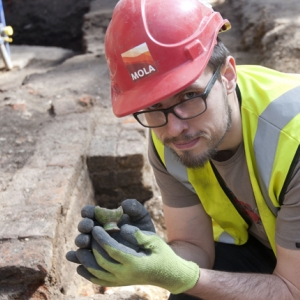 Archaeologist Paul McGarrity holds a 16th century bird whistle, a possible thatrical sound effect, discovered at Curtain theatre (c) MOLA