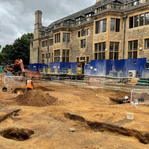 Archaeologists working on the excavation site, with Rhodes House in the background