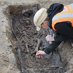 An archaeologist carefully excavates Anglo Saxon human remains and a dug-out coffin (c) MOLA