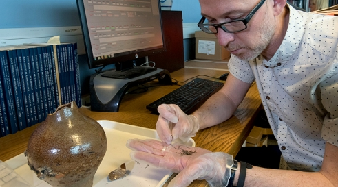 MOLA Finds Specialist Nigel Jeffries holding bent pins from inside a 'witch bottle' found during excavations at Holywell Priory (c) MOLA